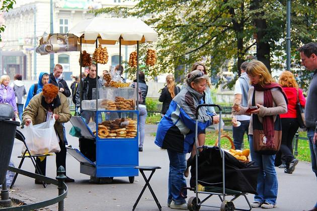 Im Vordergrund eine Brotverkäuferin mit einem Handwagen, im Hintergrund ein typischer blauer Verkaufsstand für das Hefegebäck