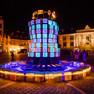 runder Turm bestehend aus blau leuchtenden Buchstabenwürfeln auf dem orangefarben beleuchteten Krakauer Markt bei Nacht
