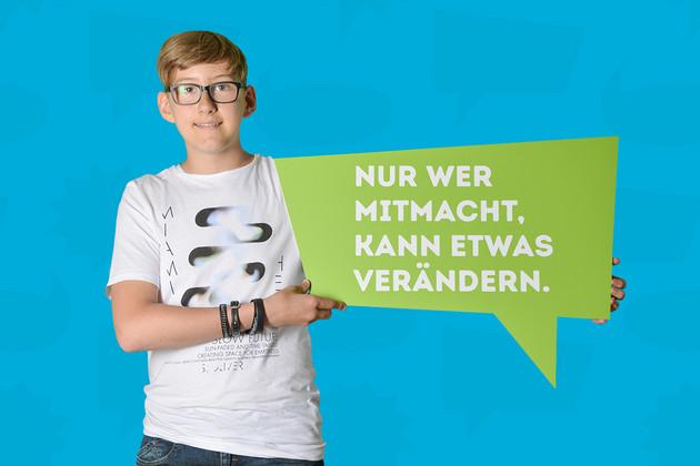 Junge zur Statementkampagne zum Jahr der Demokratie mit grüner Sprechblase auf der steht: Nur wer mitmacht, kann etwas verändern.