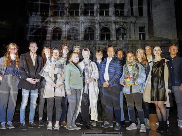 Eine Gruppe junger Menschen lächelt ins Bild. Es ist Nacht und die Gruppe wird beleuchtet.