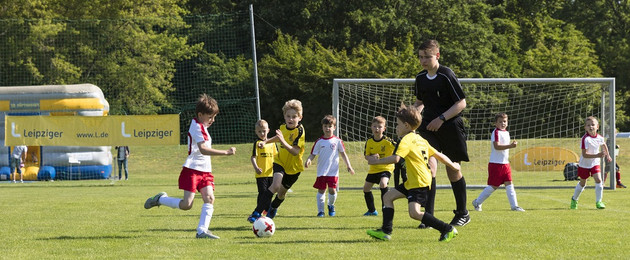 Kinder beim Fußballspiel während eines Turniers auf einem Sportplatz
