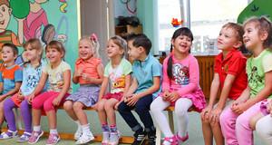 Kindergartenkinder sitzen in einer Reihe auf einer Bank in einem bunten Raum.
