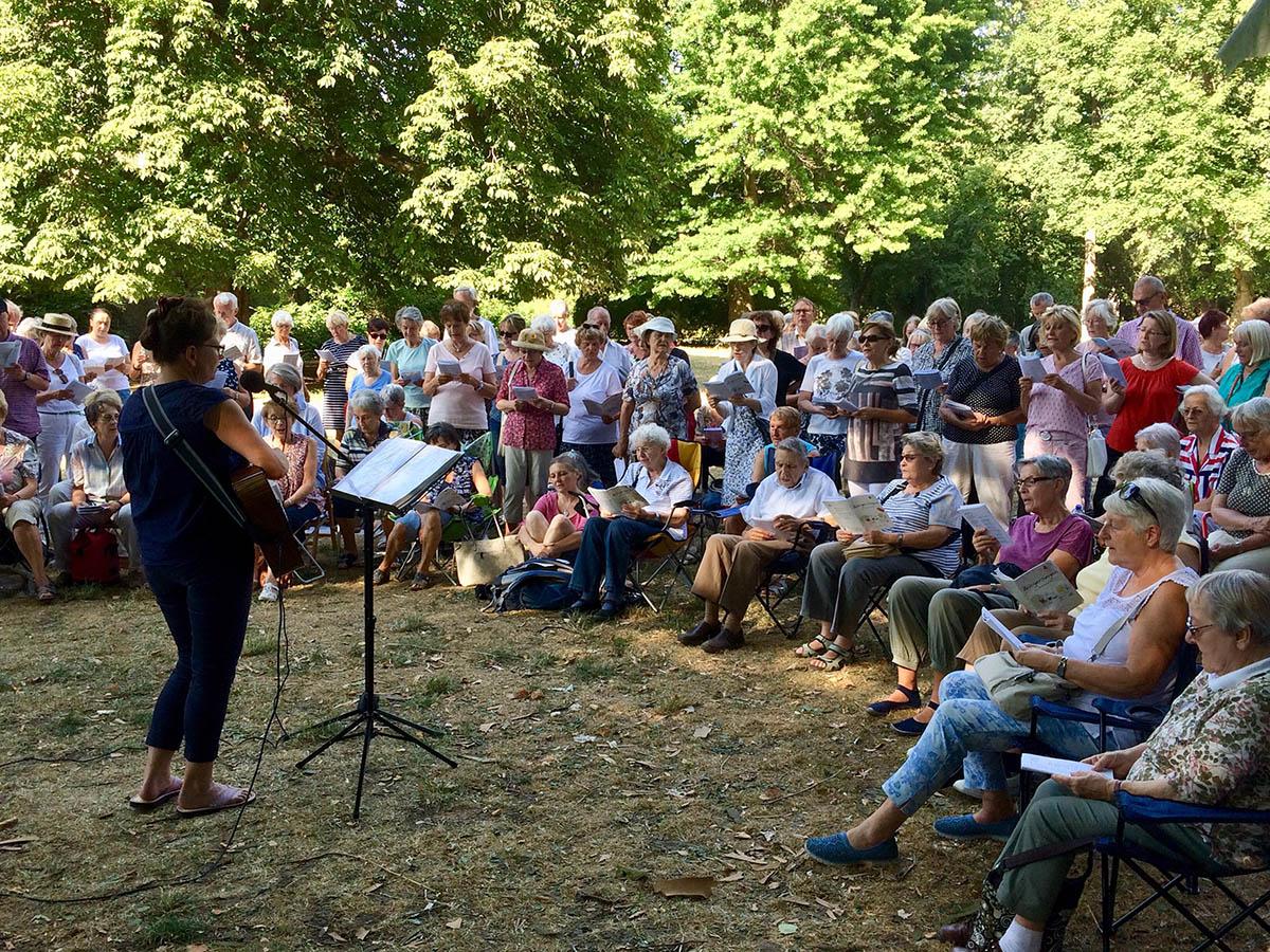 Auf eine Wiese im Park haben sich viele Menschen versammelt und singen gemeinsam. Eine Frau mit Gitarre leitet sie an.
