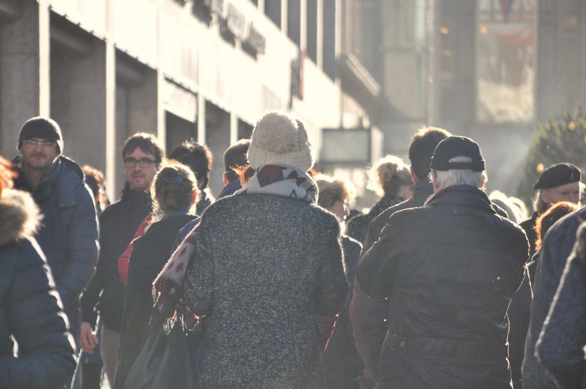 Viele Menschen sind auf einer Einkaufsstraße in der Innenstadt unterwegs
