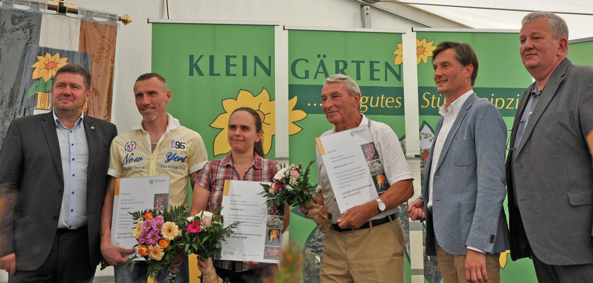 Bürgermeister Rosenthal, eine Frau und vier weitere Herren mit Blumensträußen und Urkunden in der Hand
