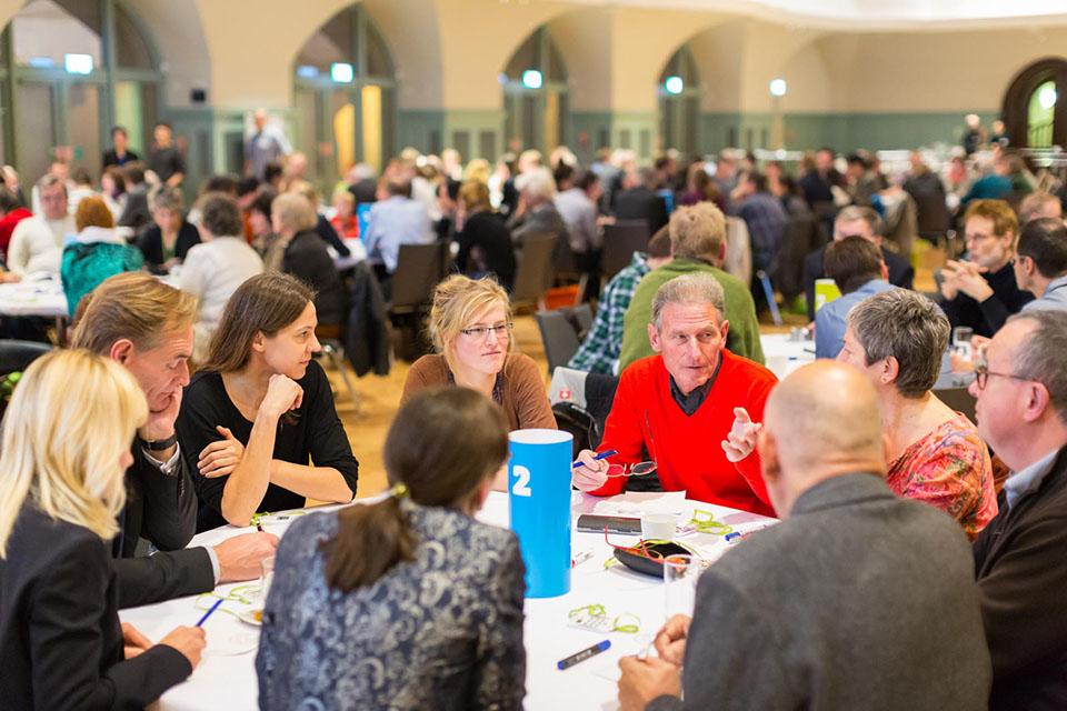 ca. 10 Menschen sitzen an einem runden Tisch, darunter Oberbürgermeister Burkhard Jung