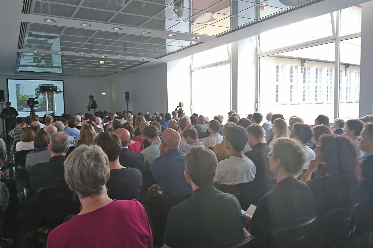 Ein Saal voller Menschen auf Stuhlreihen, die sich eine Präsentation anschauen