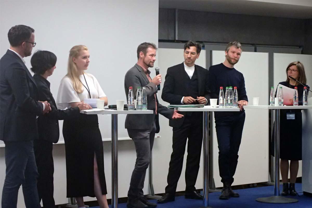 Auf einem Podium stehen drei Frauen und vier Männer mit Mikrophonen und diskutieren.