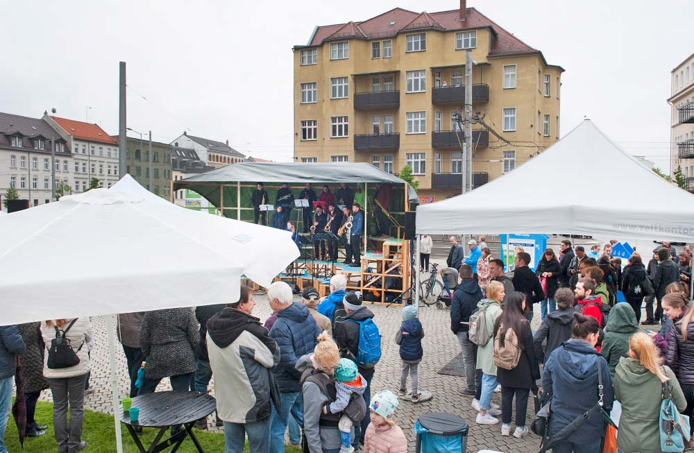 Der Huygensplatz ist voller Menschen in Regensachen, im Hintergrund stehen auf einer Bühne Musiker und eine Sängerin.