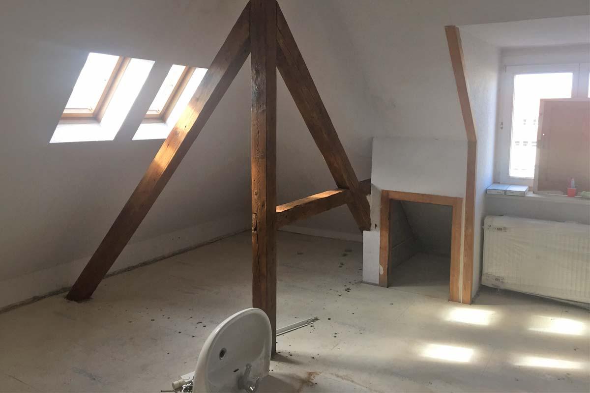 Ein Dachgeschoss wird ausgebaut, Sonne scheint durch zwei Dachfenster in den Raum, es liegt Baumaterial herum.