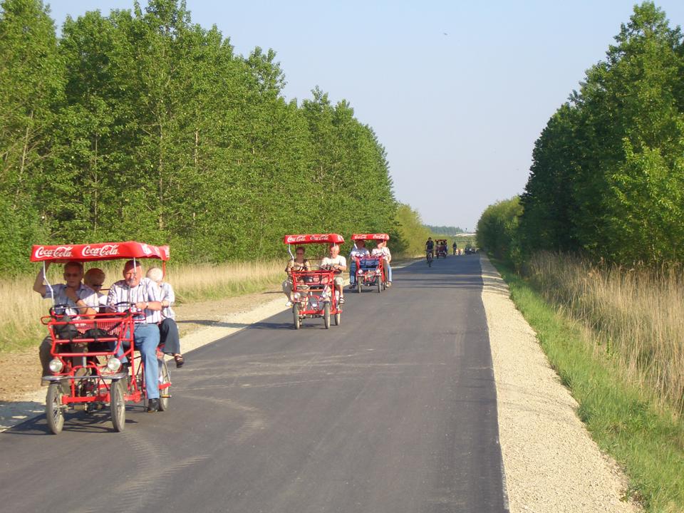 Foto des frisch asphaltierten und verbreiterten Rundwegs Cospudener See 2007 mit drei Kremserrädern und Wald